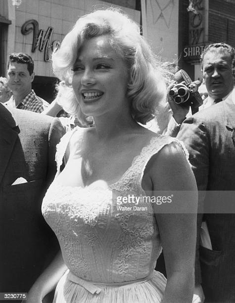 American actor Marilyn Monroe smiles in a crowd at the ribbon cutting ceremony for the opening of the TimeLIFE building Avenue of the Americas New...