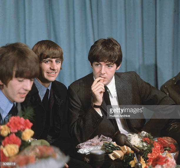 George Harrison Paul McCartney and Ringo Starr of the Liverpudlian pop group The Beatles at a press conference in London Airport following a tour of...