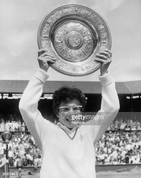 American tennis player BillieJean King lifts the trophy above her head after beating Brazil's Maria Bueno to win the women's singles title at the...