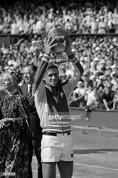 Swedish tennis player Bjorn Borg holds up the men's singles trophy for the second year running after beating Jimmy Connors in the final at the...