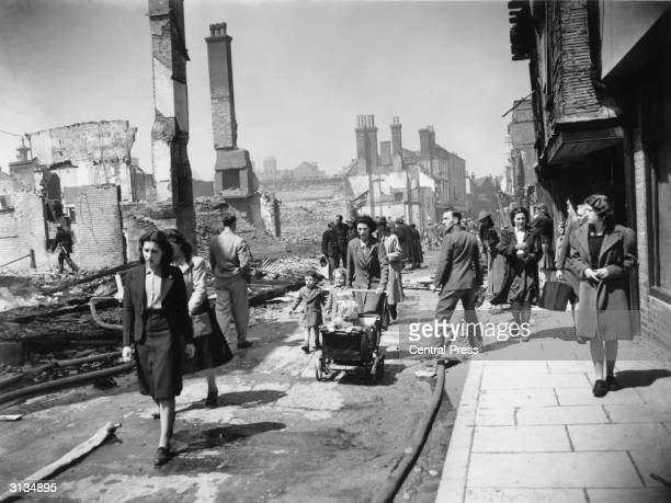 A crowd of men women and children make their way through the devastated streets of Canterbury left homeless by a recent World War II bombing raid