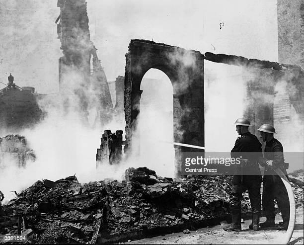 Firemen hosing down the English Shrine after a German bombing raid on Canterbury
