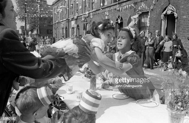 A child is passed across the table at a party in Morpeth Street in London's East End to celebrate the coronation of Queen Elizabeth II The girl...