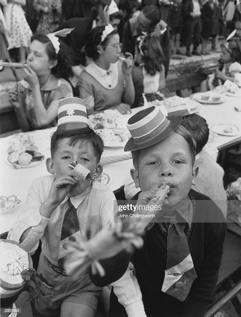 A couple of East End boys blowing paper whistles at a street party held in Morpeth Street, London, during Queen Elizabeth II's Coronation celebrations. The boy on the right is Ted Lewis. Original Publication: Picture Post - 6542 - Cockneys' Own Party - pub.1953