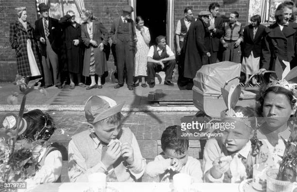 Children stuffing themselves with food at a party in Morpeth Street in London's East End to celebrate the coronation of Queen Elizabeth II The girl...