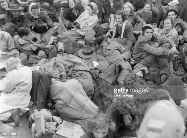 Crowds waking up in the rain after spending all night sleeping in Trafalgar Square before Queen Elizabeth II's Coronation