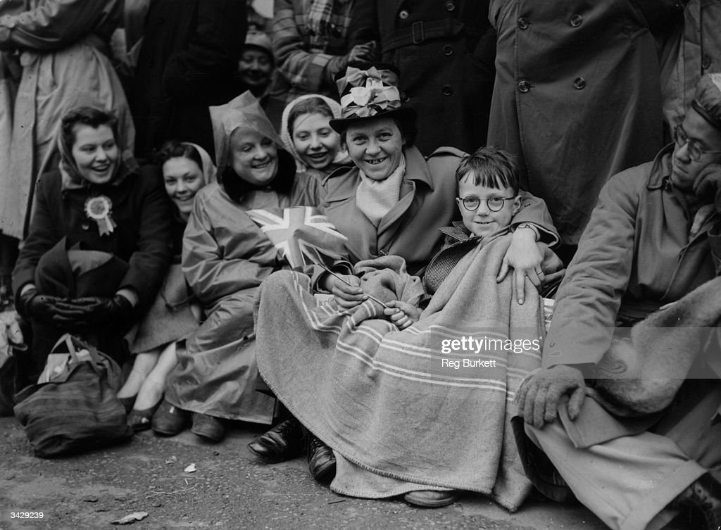 Mrs Birch and her eight-year-old son John, who have been sitting in the Mall outside London's Buckingham Palace since yesterday morning in order to be present for the coronation of Queen Elizabeth II. Mrs Birch is wearing a patriotic top hat decorated with red, white and blue ribbons.