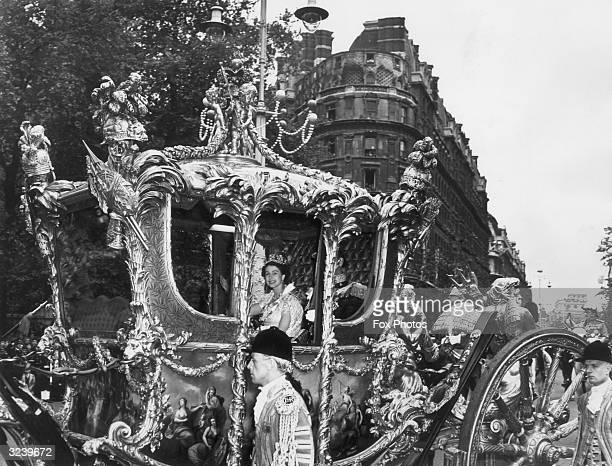 Queen Elizabeth II and Prince Philip make their way to Westminster Abbey in a gilded coach for the Queen's coronation