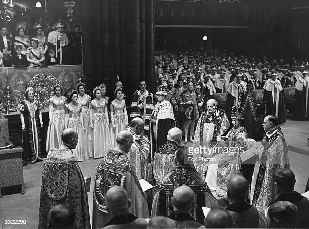 Queen Elizabeth II holds the rod with dove in her left hand and the sceptre with cross in her right hand at her coronation ceremony. She is...