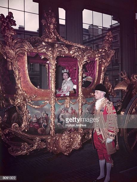 Queen Elizabeth II in the coronation coach on her way to be crowned at Westminster Abbey. She is dressed as a peeress of the realm and wears the...