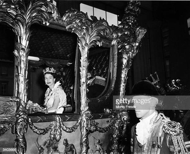 Queen Elizabeth II looking out from her carriage en route to Westminster Abbey for her Coronation ceremony