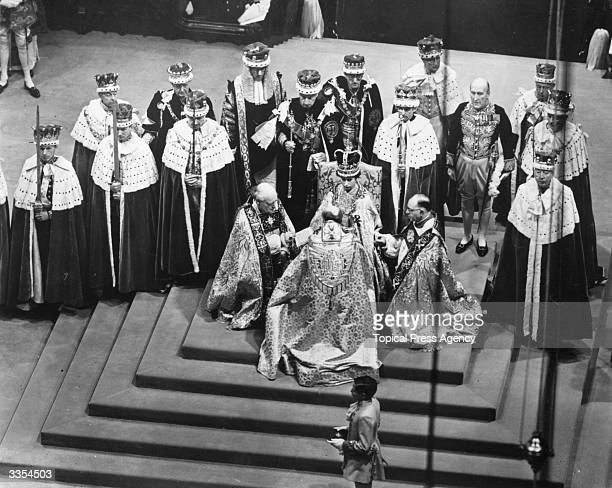 Queen Elizabeth II seated on a throne in Westminster Abbey attended by dignitaries whilst Bishops pay homage to her