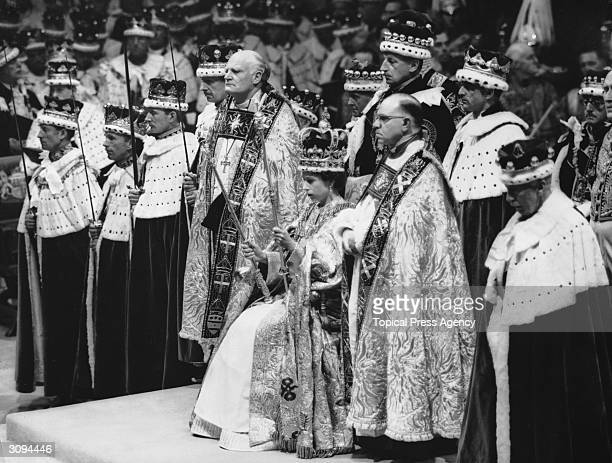 Queen Elizabeth II seated upon the throne at her coronation in Westminster Abbey London She is holding the royal sceptre and the rod with the dove