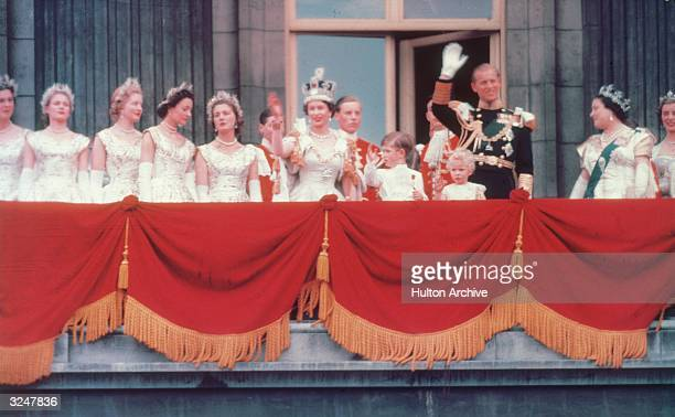 The Duke of Edinburgh and the newly crowned Queen Elizabeth II wave to the crowd from the balcony at Buckingham Palace Her children Prince Charles...