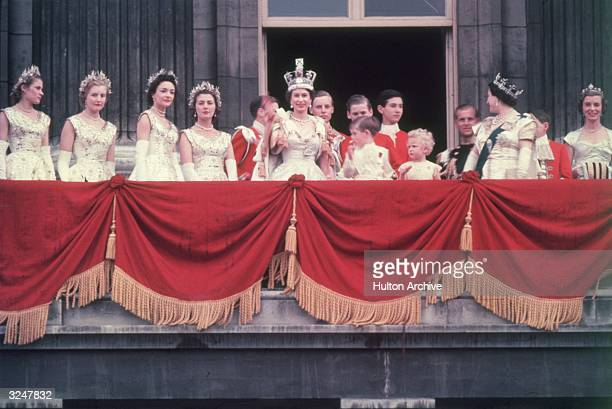 The newly crowned Queen Elizabeth II waves to the crowd from the balcony at Buckingham Palace. Her children Prince Charles and Princess Anne stand...