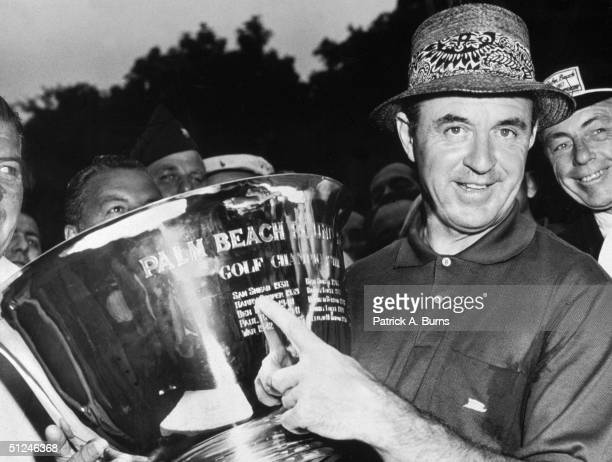 2nd June 1957 American golfer Sam Snead holds the victory cup after the Palm Beach 'Round Robin' golf tournament and points to his dated name on the...