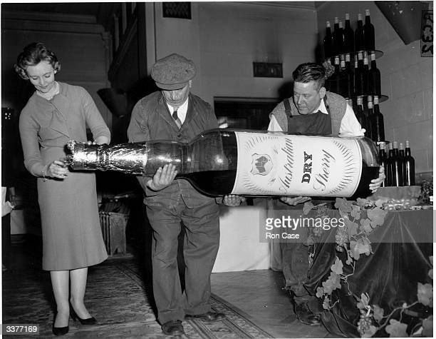 Dawn Lefevre receiving a glass of sherry from a giant bottle during a party at Australia House in London