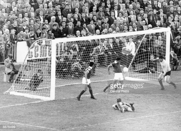 Spain's monopoly of the European Cup is ended as Benfica player Angelo stops the ball from crossing the goal line with his chest helping his side to...