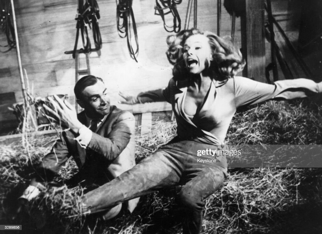 Sean Connery as James Bond up to his tricks with actress Honor Blackman during the filming of 'Goldfinger' at Pinewood studios. The film was directed by Guy Hamilton.