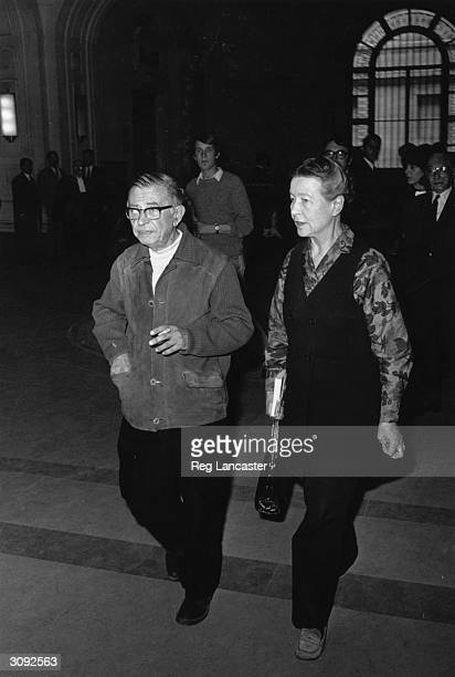 Author dramatist and novelist Jean Paul Sartre and existentialist writer and a winner of the Prix Goncourt Simone de Beauvoir leaving the Palais de...