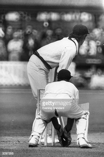 Wicket keeper John Murray appears to be unaware that his trousers have split at the seams exposing part of his buttocks