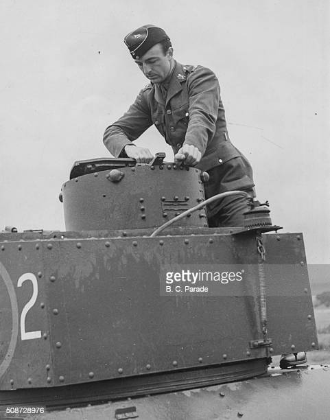 2nd Lieutenant John Profumo who will later become a British politician pictured standing on a light tank at a training camp at Houghton Bridge...