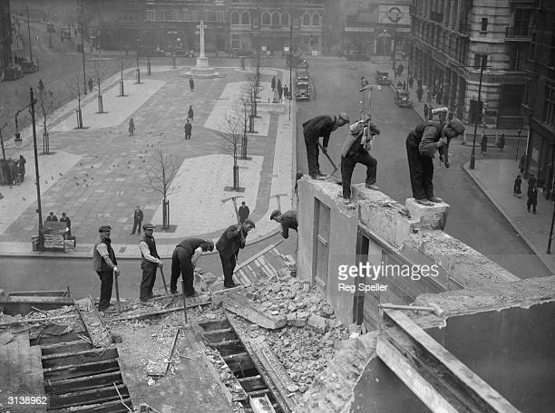 Demolition workers balance on walls in Sloane Square London where shops are being pulled down to make way for the building of the new Peter Jones...