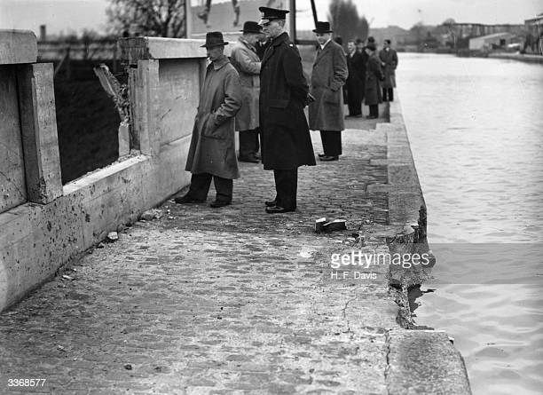 CID officers examine terrorist bomb damage on the aqueduct carrying the Grand Union canal over the North Circular Road at Willesden in London