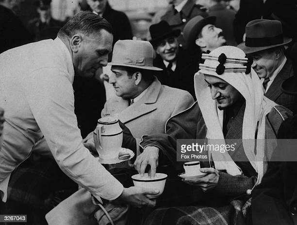 Prince Faisal of Saudi Arabia , later King Faisal, takes a coffee break during a visit to RAF Northolt in London to watch a flying display.