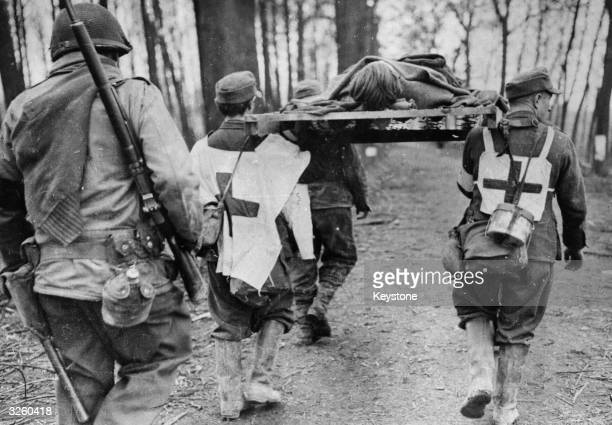 Two captured German medics wearing large Red Crosses for identification and two other captured German soldiers carry a wounded comrade to the...