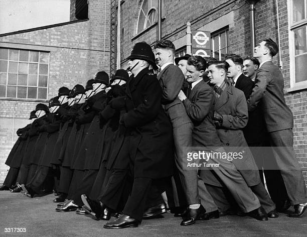 A line of police constables in training for the enormous crowds expected at Queen Elizabeth II's Coronation practising the 'linked arms' method of...