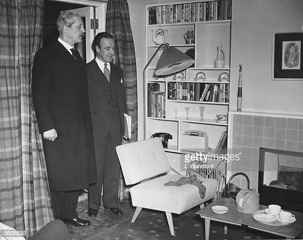 Harold Macmillan British housing minister and Ernest Marples Parliamentary Secretary to the Ministry view the lounge in the People's House at the...