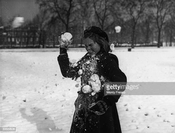 Young girl being hit by a snowball whilst playing in St James Park, London, after a night of heavy snowfall.
