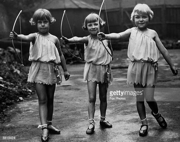 Three members of the 'Rosebud' dancing troupe seen here dressed as Cupid during rehearsals for their annual display at the Alexandra Palace London