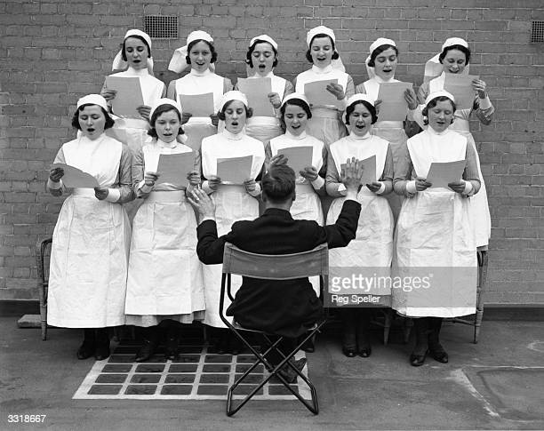 A choir of nurses rehearsing their performance for the opening of the King George V extension at Moorfields Eye Hospital London