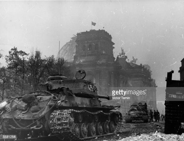 The Red Flag flies over the Reichstag as Russian tanks roll through Berlin The 152 heavy tank tank in the foreground has the name 'Combat Girlfriend'...