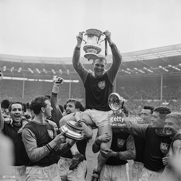 West Ham United captain Bobby Moore holding the FA Cup is held aloft by his team mates after their 32 victory over Preston North End in the FA Cup...
