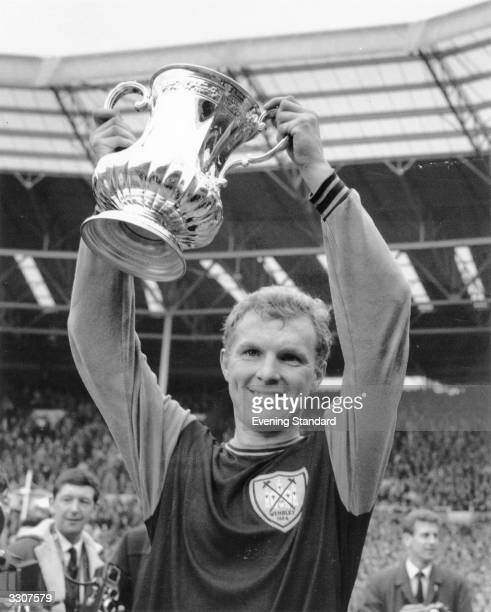 West Ham United captain Bobby Moore lifts the FA Cup trophy after his team's 32 victory over Preston North End in the final at Wembley