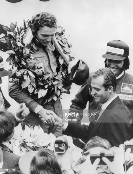 Austrian Formula 1 racing driver Niki Lauda is congratulated by Prince Juan Carlos after winning the Spanish Grand Prix at the Jarama Circuit,...