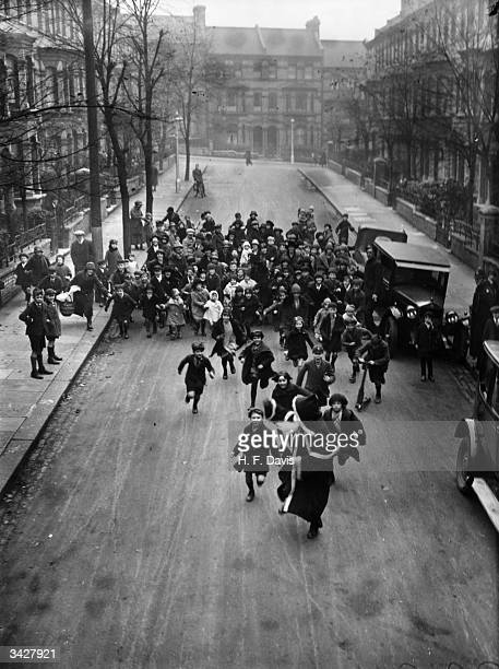 A crowd of happy youngsters chase Father Christmas along a London street He is on his way to a south London store to distribute presents