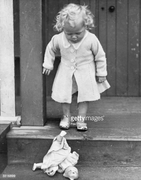 A little girl about to burst into tears as she realises that her doll is broken