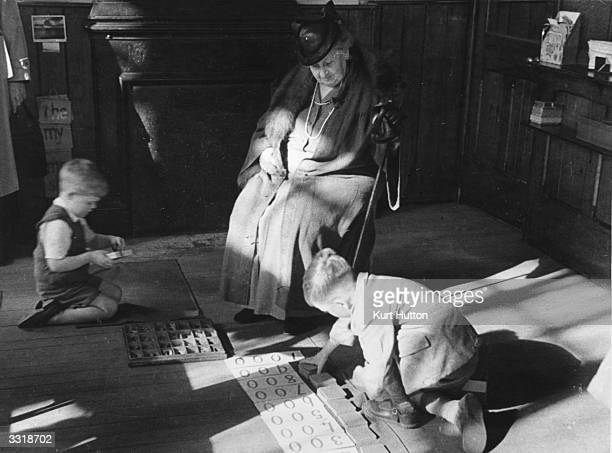 Italian educationist and founder of the Montessori Schools Maria Montessori watching a couple of boys working in a classroom in Acton London Original...