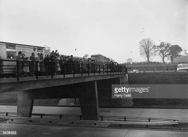 A crowd on a bridge watching the opening by Ernest Marples British Minister of Transport of the London to Birmingham motorway 72 miles long and Great...