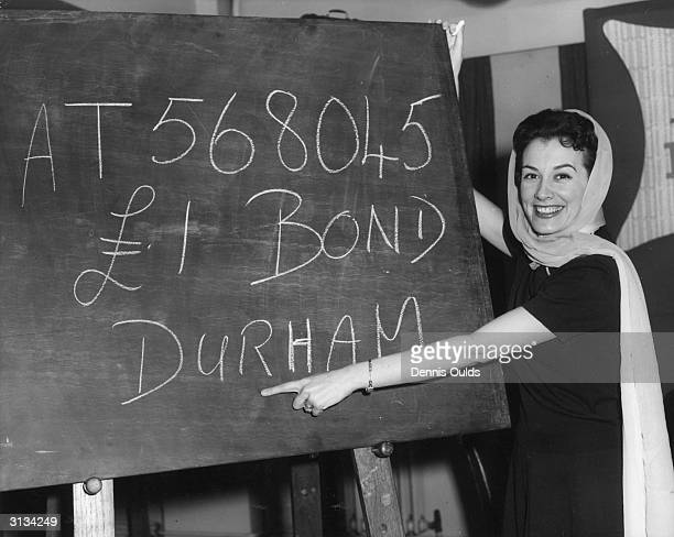 Anne Rogers the star of the West End show 'My Fair Lady' with the first one thousand pound prize winning premium bond number which belongs to a saver...