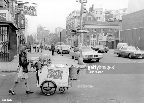 A woman pushing her ice cream and pretzel cart on Second Avenue