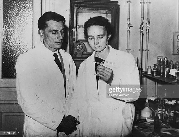 Irene JoliotCurie daughter of Marie and Pierre Curie and a nuclear physicist stands in the laboratory with her husband Jean Frederic JoliotCurie also...