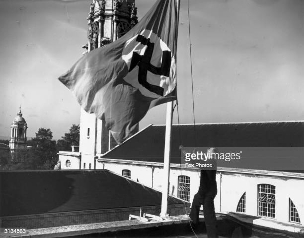 By order of the Lord Mayor the swastika flag is hoisted again above Cardiff City Hall where it hangs alongside British French and Italian flags It...