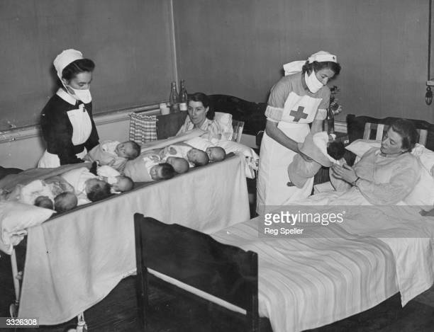 Nurses bringing babies by trolley to their mothers for feeding at Shardloes stately home, Amersham, Buckinghamshire. Over 3,000 babies of London...