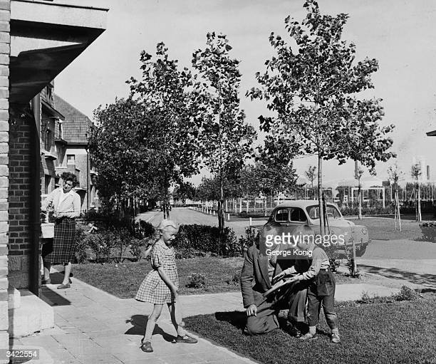 A father plays with his two children outside their house which is in the vicinity of the Dunkirk oil refinery where he works
