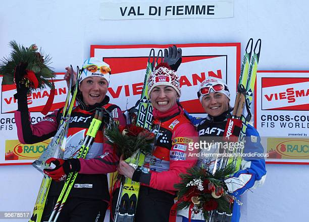 2nd Petra Majdic of Slovenia 1st Justyna Kowalczyk of Poland and 3rd Arianna Follis of Italy celebrate their success during the final climb women for...